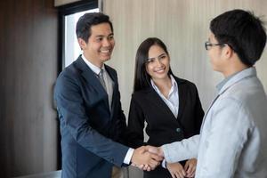 empresários asiáticos apertando as mãos e sorrindo concordando para assinar o contrato e encerrar uma reunião foto