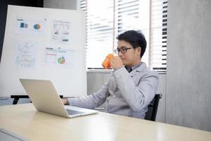 empresário tomando café e trabalhando no escritório foto