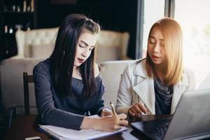duas mulheres de negócios asiáticas usando notebook trabalhando e discussão do importante contrato no escritório foto