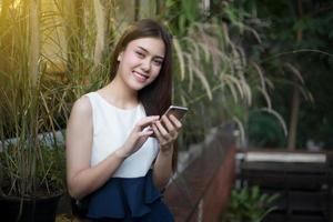 As mulheres asiáticas estão sorrindo e usando celulares e telefones inteligentes para se comunicar e verificar como estão os executivos ao ar livre na cafeteria foto