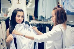 dois sorridentes jovem asiática com compras e compra no supermercado de shopping foto