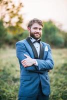 Noivo bonito em terno de casamento postando no parque foto
