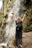 mulher em pé na ponte olhando para a bela cachoeira da montanha foto
