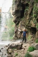 mulher caminhando pela bela cachoeira da montanha foto