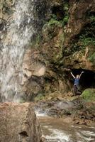 pequeno humano observando na bela cachoeira da montanha foto