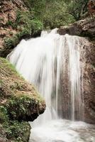 bela cachoeira na montanha capturada com desfoque de movimento foto