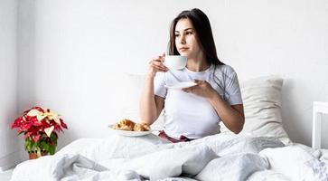jovem morena sentada acordada na cama com balões em forma de coração vermelho e decorações, bebendo café comendo croissants foto