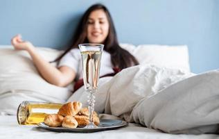 jovem morena sentada acordada na cama com balões em forma de coração vermelho e decorações bebendo champanhe comendo croissants foto