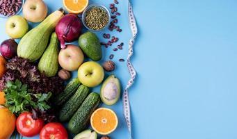 vegetais frescos e frutas para uma dieta saudável e uma fita métrica vista de cima plana com espaço de cópia foto