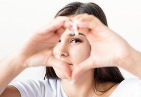 jovem mulher morena feliz em uma camiseta branca mostrando o sinal de um coração com as mãos na frente do rosto foto