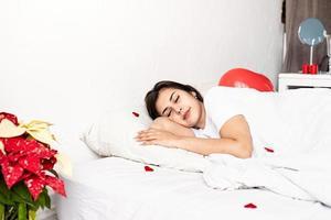 jovem morena dormindo na cama com balões em forma de coração vermelho e decorações foto