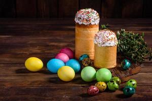 bolo de páscoa e ovos coloridos em um fundo escuro foto