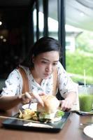 mulheres asiáticas sorrindo e felizes e gostando de comer hambúrgueres no café e no restaurante na hora do relaxamento foto