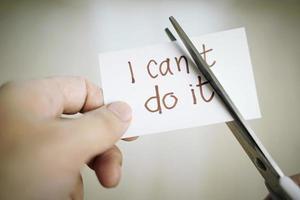 mão de homem cortando nota de papel com tesoura para remover a palavra de não consigo fazer textos. atitude positiva, conceito de autoconfiança e motivação foto