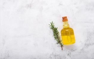 frasco de vidro de azeite e ramo de alecrim criado em fundo branco de concreto. foto