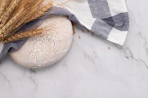 massa fresca de fermento caseiro descansando na mesa de mármore com espigas de trigo e rolo. foto