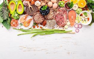 conceito de dieta de baixo teor de carboidratos cetogênica. ingredientes para seleção de alimentos saudáveis configurados em fundo branco de madeira. foto