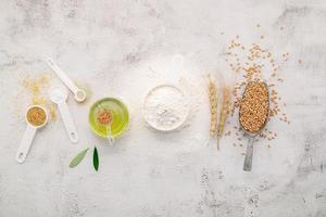 os ingredientes para massa de pizza caseira com espigas de trigo, farinha de trigo e azeite montados em fundo branco de concreto. vista de cima e copie o espaço. foto