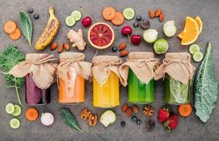 smoothies saudáveis coloridos e sucos em garrafas com frutas tropicais frescas e superalimentos em fundo de pedra escura com espaço de cópia. foto