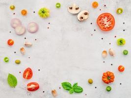 os ingredientes para pizza caseira montada em fundo branco de concreto. foto