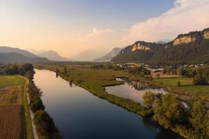 vista aérea de um rio e campo ao pôr do sol foto