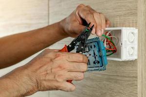 eletricista está removendo fios elétricos em uma caixa de plástico em uma parede de madeira para instalar a tomada elétrica. foto