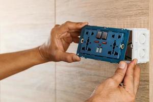 mão de um eletricista está instalando o plugue de alimentação CA da tomada de parede universal com porta USB e liga-desliga em uma caixa de plástico em uma parede de madeira. foto