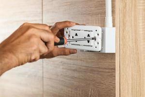 O eletricista está usando uma chave de fenda para instalar a tomada elétrica em uma caixa de plástico em uma parede de madeira. foto