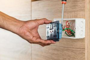 A mão de um eletricista está usando uma chave de fenda para conectar os fios ao plugue de alimentação CA da tomada de parede universal com porta USB e liga-desliga em uma caixa de plástico em uma parede de madeira. foto