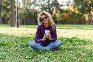 mulher linda tomando café no parque foto
