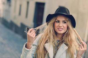 mulher olhando com seu cabelo loiro encaracolado em meio urbano foto