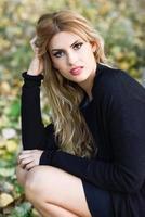 jovem mulher com longos cabelos loiros cacheados em parque urbano foto