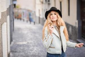 Mulher jovem e bonita com cabelo encaracolado e chapéu foto