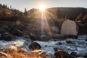 pôr do sol brilhando na floresta de pinheiros com cachoeira fluindo no parque nacional foto