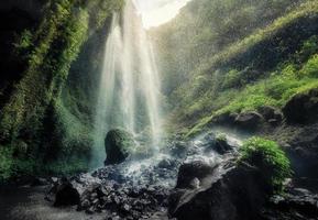 bela cachoeira madakaripura fluindo em rochoso no riacho foto