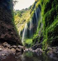 bela cachoeira madakaripura fluindo em vale verde foto