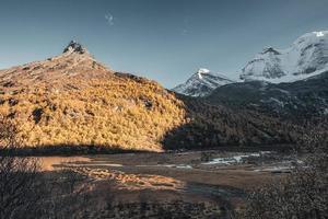 montanha sagrada com céu azul em uma floresta de pinheiros no outono na reserva natural yading foto