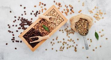 grãos de café torrados escuros e não torrados descafeinados verdes e marrons em caixa de madeira com colheres configuradas em fundo branco de concreto. foto