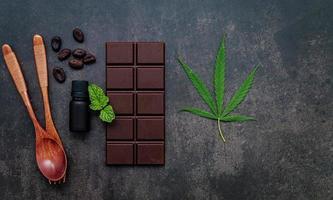 comida imagem conceitual de folha de cannabis com chocolate escuro e garfo no fundo escuro de concreto. foto