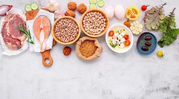 conceito de dieta de baixo teor de carboidratos cetogênica. ingredientes para seleção de alimentos saudáveis configurados em fundo branco de concreto. foto