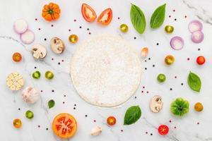 os ingredientes para pizza caseira montada em fundo de mármore branco. foto