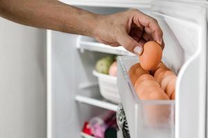 mãos humanas colocam ovos de galinha no compartimento de postura da geladeira. foto