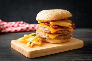 hambúrguer de porco com queijo, bacon e batata frita foto