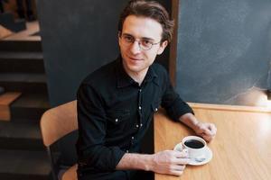 bonito homem barbudo de camisa xadrez segurando um garfo, comendo no café e sorrindo, olhando para a câmera foto