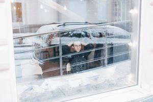jovem tomando café em um café, olhando pela janela foto