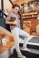 jovem talentoso na camisa casual desenhando o esboço no caderno, aproveitando o tempo de lazer no café. estudante qualificado escrevendo a lição de casa no bloco de notas sentado no coworking foto