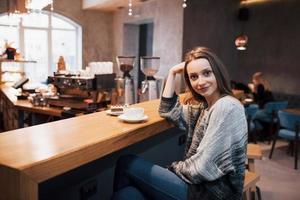 jovem atraente sentado no interior do café urbano. estilo de vida da cidade de café. retrato casual de adolescente. tonificado. foto
