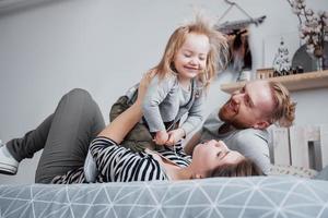 família feliz mãe, pai e filha rindo na cama foto