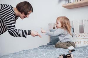 família amorosa feliz. mãe e filha menina brincando e se abraçando foto