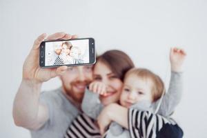 família, feriados, tecnologia e pessoas - sorrindo, mãe, pai e filha fazendo selfie com a câmera sobre fundo branco foto